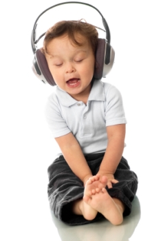 Picture of cute toddler girl, white shirt and jeans, wearing music headphones, singing holding her toes