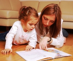 A picture of a mom and a three year old learning from a home schooling book