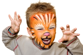 toddler art activities picture, shows cute little boy wearing face painting, orange white and red, with his hands outstretched and a mock scary face
