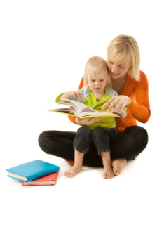Photo of a mother reading with her blonde toddler son with other books on the floor.