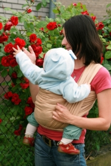 picture of baby in a sling with mom looking at flowers on baby sign language website