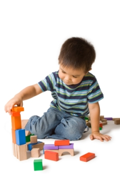 photograph of little toddler boy in a striped shirt, building blocks displaying the idea of home activities for toddlers